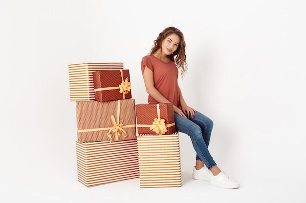 Giovane bella donna che si siede sul grande contenitore di regalo