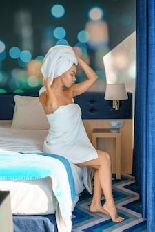 Giovane bella donna che si siede sul letto in asciugamano, mattina di concetto.