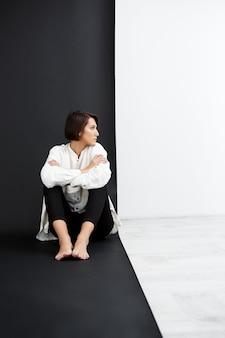Giovane bella donna che si siede sul pavimento sopra la superficie in bianco e nero