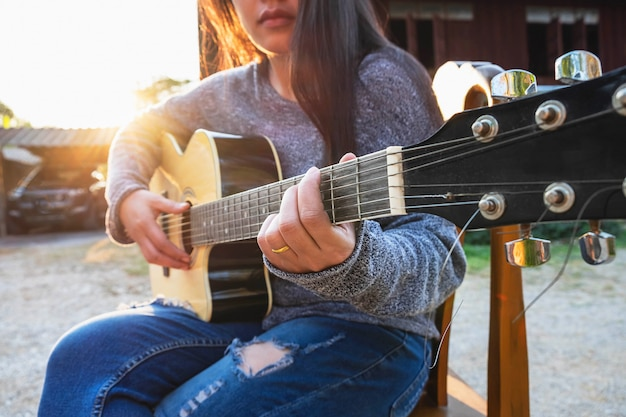 Giovane bella donna che si siede sulla sedia che compone una canzone