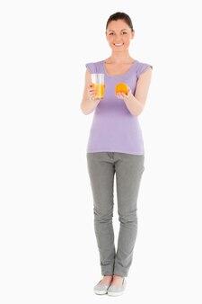 Giovane bella donna che tiene un'arancia e un bicchiere di succo d'arancia