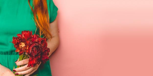 Giovane bella donna che tiene un mazzo della molla dei tulipani rossi in sua mano.