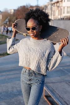 Giovane bella donna che tiene uno skateboard