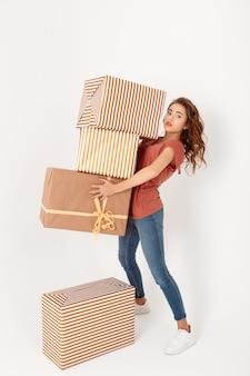 Giovane bella donna che trasporta grandi contenitori di regalo