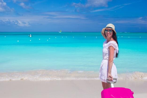 Giovane bella donna con bagagli colorati sulla spiaggia tropicale