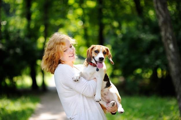 Giovane bella donna con cane beagle nel parco estivo. amorevole proprietario femminile con il suo animale domestico domestico