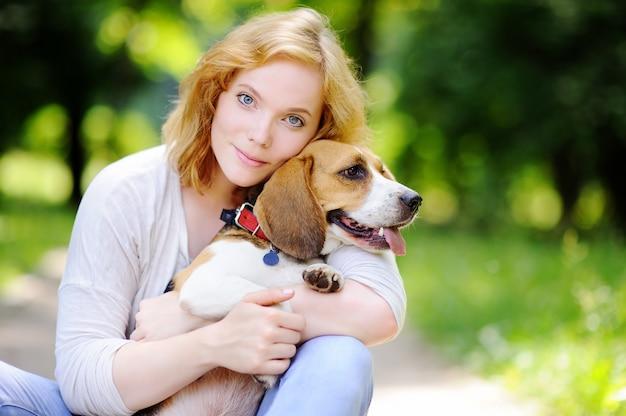 Giovane bella donna con cane beagle nel parco estivo