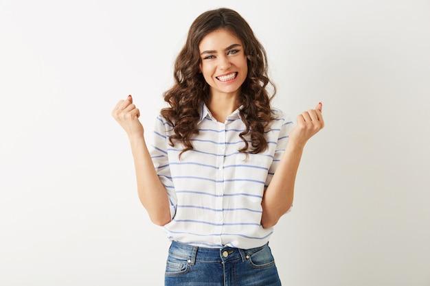 Giovane bella donna con espressione del viso emotivo, alzando le mani, successo, vincitore, stile casual, isolato, felice, stato d'animo positivo, sorriso sincero, capelli ricci lunghi, denti bianchi, forte, indipendente