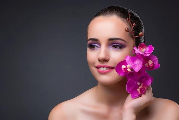 Giovane bella donna con fiore orchidea