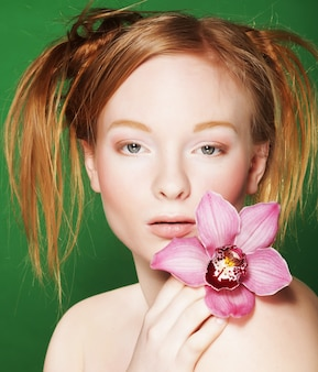 Giovane bella donna con fiore rosa