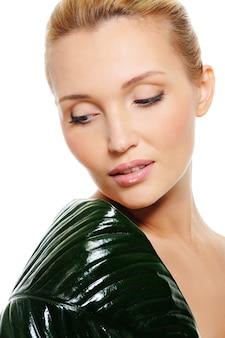 Giovane bella donna con foglia verde che copre la spalla