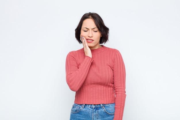 Giovane bella donna con guancia e mal di denti dolorosi, sentirsi male, miserabile e infelice, in cerca di un dentista contro il muro bianco