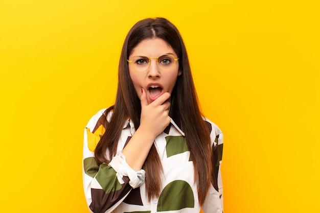 Giovane bella donna con la bocca e gli occhi spalancati e la mano sul mento, sentendosi spiacevolmente scioccata, dicendo cosa o wow contro il muro giallo