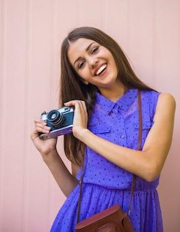 Giovane bella donna con la macchina fotografica vecchio stile.
