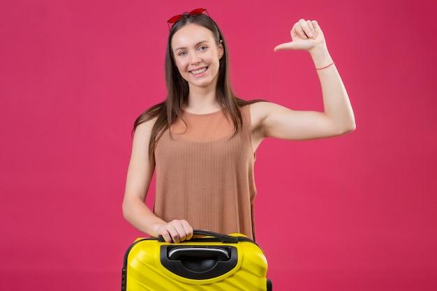 Giovane bella donna con la valigia di viaggio che indica se stessa con il pollice che sorride allegramente in piedi sopra la parete rosa