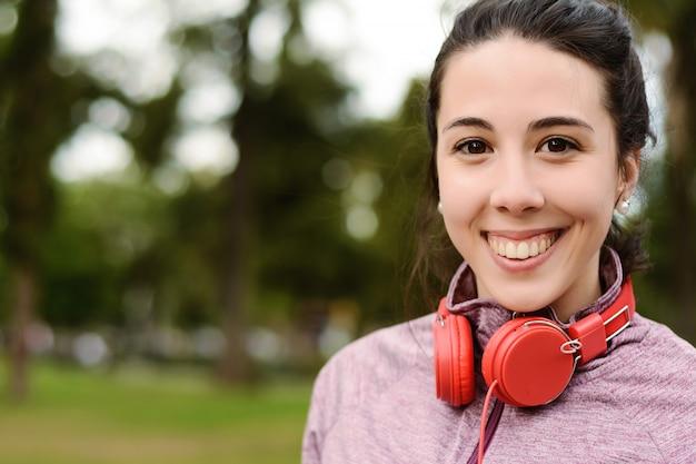 Giovane bella donna con le cuffie rosse ascolto musica