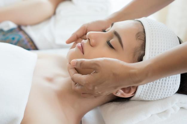 Giovane bella donna con massaggio viso rilassante nella spa.