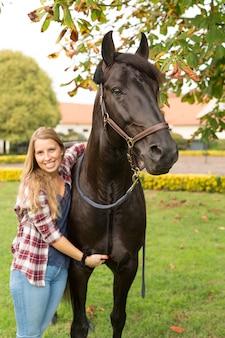 Giovane bella donna con un cavallo
