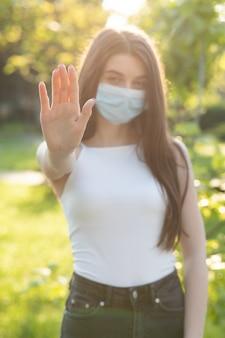 Giovane bella donna con una maschera nel parco