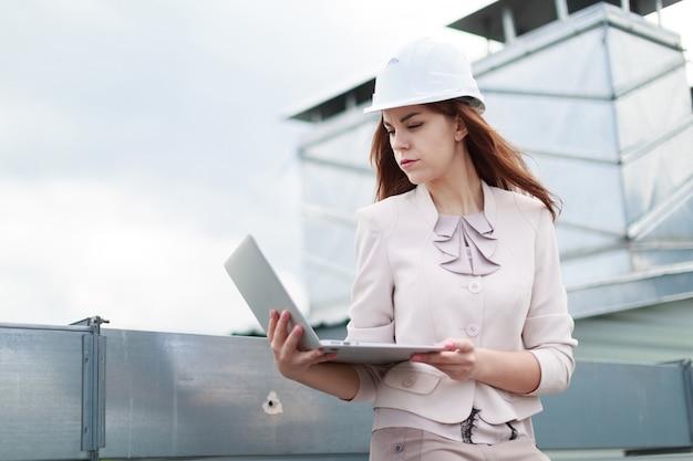Giovane, bella donna d'affari in abito beige, pantaloni marroni e casco sedersi sul tetto e tenere il portatile