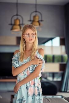 Giovane bella donna degli occhi azzurri e biondi con la mano sul mento che pensa alla domanda, espressione pensierosa.