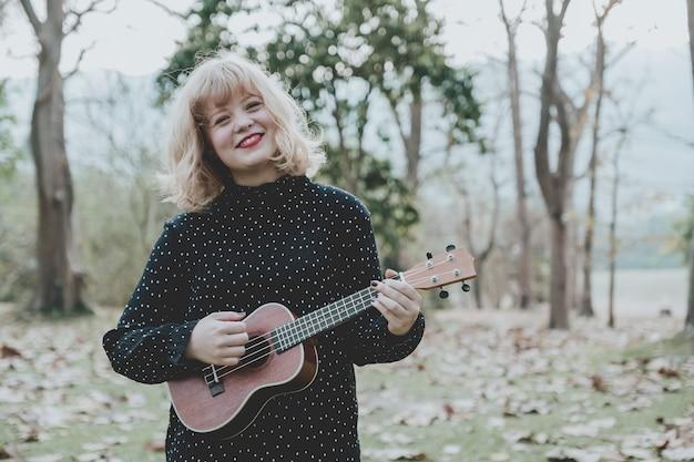 Giovane bella donna dei pantaloni a vita bassa nel parco che gioca le ukulele e che smilling tono d'annata