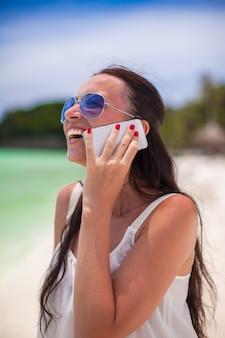 Giovane bella donna del primo piano alla spiaggia che parla sul suo telefono