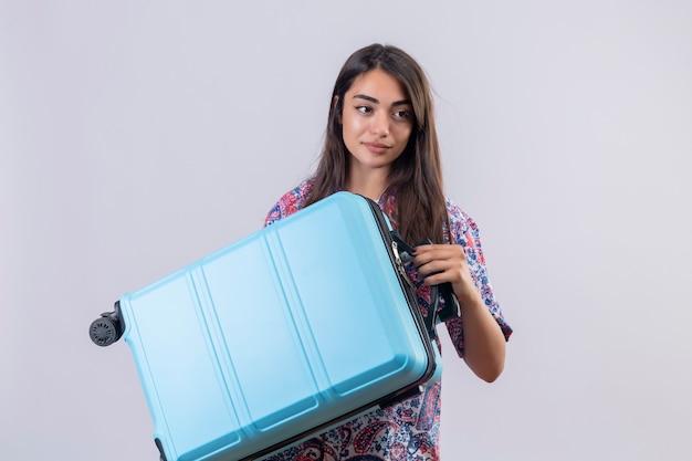 Giovane bella donna del viaggiatore che tiene la valigia blu che osserva da parte con il sorriso sicuro che sta sopra fondo bianco