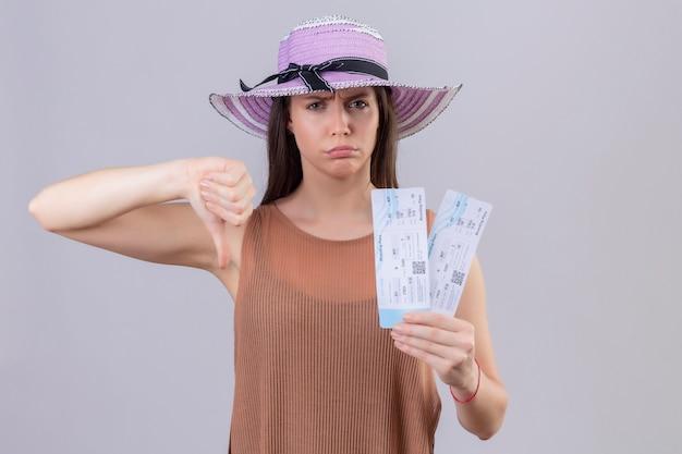 Giovane bella donna del viaggiatore in biglietti di aria della tenuta del cappello di estate con il fronte aggrottante le sopracciglia che mostra i pollici giù sopra la parete bianca