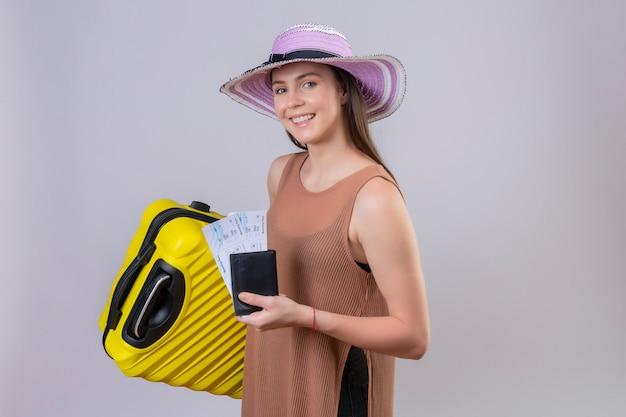 Giovane bella donna del viaggiatore in cappello di estate che tiene valigia gialla e biglietti che sorridono con il fronte felice sopra la parete bianca