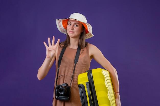 Giovane bella donna del viaggiatore in cappello estivo con la valigia gialla e la fotocamera sorridente positivo e felice che mostra il numero tre in piedi su sfondo viola