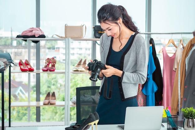 Giovane bella donna dell'asia che prende una foto e che lavora all'acquisto online di commercio elettronico al negozio di vestiti.