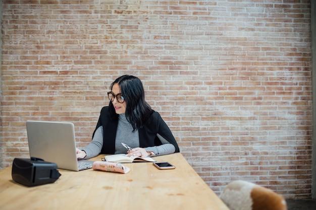 Giovane bella donna dell'interno facendo uso dello scrittorio di seduta di computer