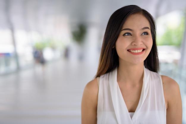 Giovane bella donna di affari asiatica che va in giro alla passerella