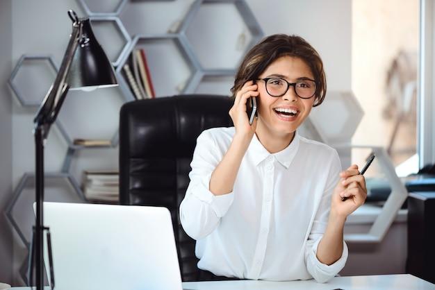 Giovane bella donna di affari sorridente che parla sul telefono nel luogo di lavoro in ufficio.