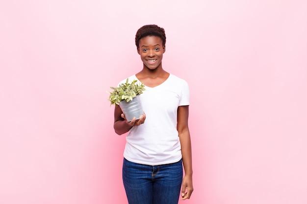 Giovane bella donna di colore che sembra felice e piacevolmente sorpresa, eccitata con un'espressione affascinata e scioccata che tiene una pianta