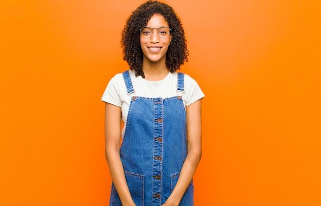 Giovane bella donna di colore che sembra felice e piacevolmente sorpresa, eccitata con un'espressione affascinata e scioccata contro la parete arancione