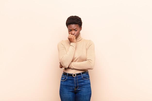 Giovane bella donna di colore che si sente seria, premurosa e preoccupata, fissando di lato con la mano premuta contro il mento