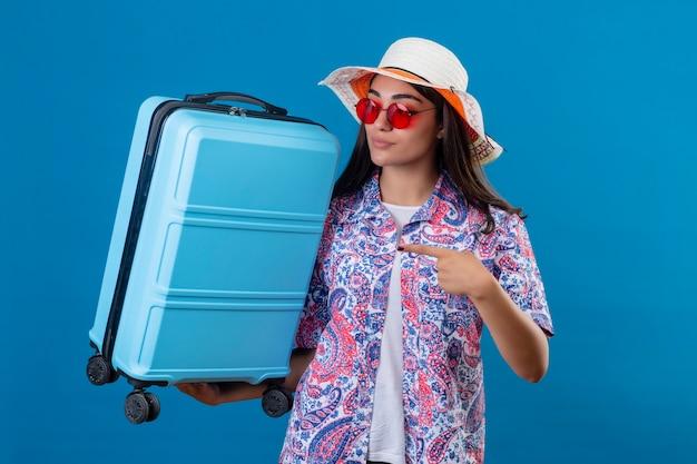 Giovane bella donna di viaggiatore che indossa un cappello estivo e occhiali da sole rossi che tiene la valigia di viaggio che indica con il dito con espressione facciale seria fiduciosa in piedi sopra la parte posteriore blu isolata