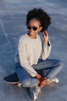 Giovane bella donna di vista frontale che si siede su uno skateboard