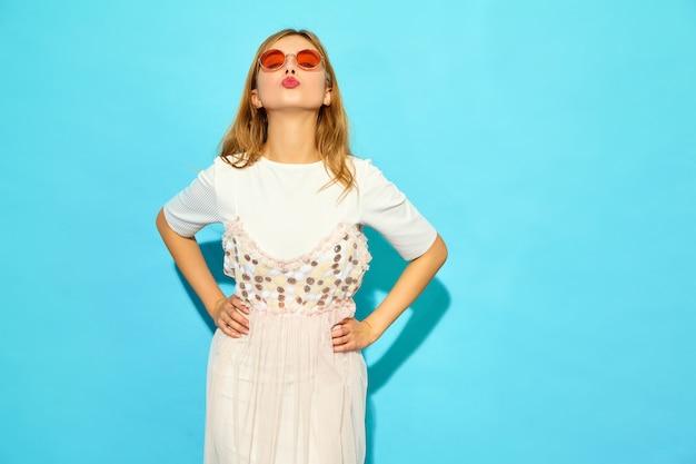 Giovane bella donna donna alla moda in abiti casual estivi in occhiali da sole. modello divertente isolato sulla parete blu