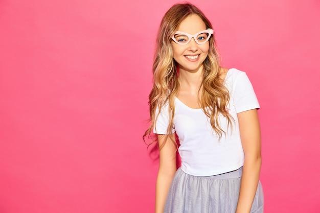 Giovane bella donna donna alla moda in abiti estivi casual in occhiali da sole falsi oggetti di scena. linguaggio del corpo positivo di emozione femminile di espressione facciale. modello divertente isolato sulla parete rosa