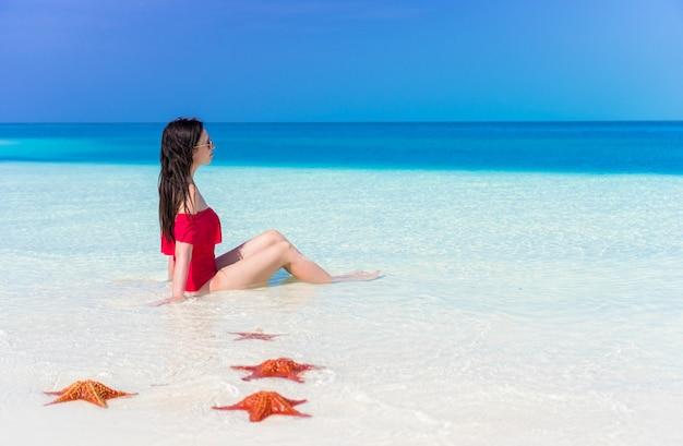 Giovane bella donna durante la vacanza tropicale della spiaggia