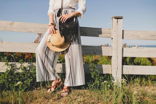 Giovane bella donna elegante, tendenza moda primavera estate, stile boho, cappello di paglia, weekend in campagna, sole, sorridente, divertimento, occhiali da sole, borsa nera, pantaloni a righe, dettagli, accessori