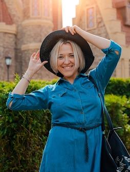 Giovane bella donna felice alla moda contro il centro storico medievale