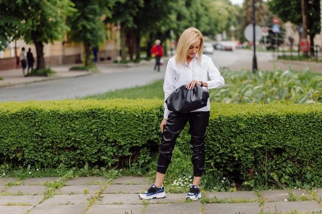 Giovane bella donna felice che per mezzo del suo smart phone che cammina sulla via della città