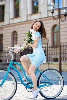 Giovane bella donna felice che sorride allegro che si siede su una bicicletta nella via della città