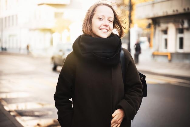 Giovane bella donna felice della ragazza in un cappotto e una sciarpa su una via soleggiata di autunno