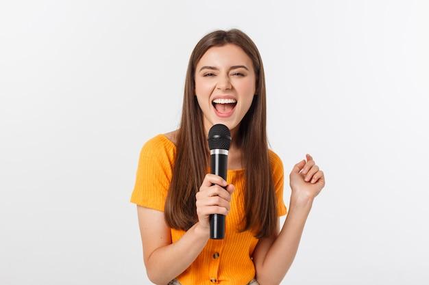 Giovane bella donna felice e motivata, cantando una canzone con un microfono, presentando un evento o una festa, goditi il momento
