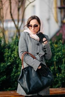 Giovane bella donna felice in un cappotto che propone al parco